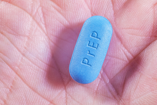 A hand holding a pill labelled PrEP - Pre-Exposure Prophylaxis for HIV / AIDS