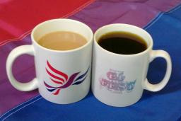 A Bisexual Liberal Democrats mug, and a Brighton BiFest mug, on a Bi Flag, containing tea and coffee